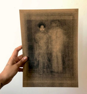 A hand holds a print. The print is of a golden image of what appears to be two figures (a man and a woman) standing. Everything is gold.