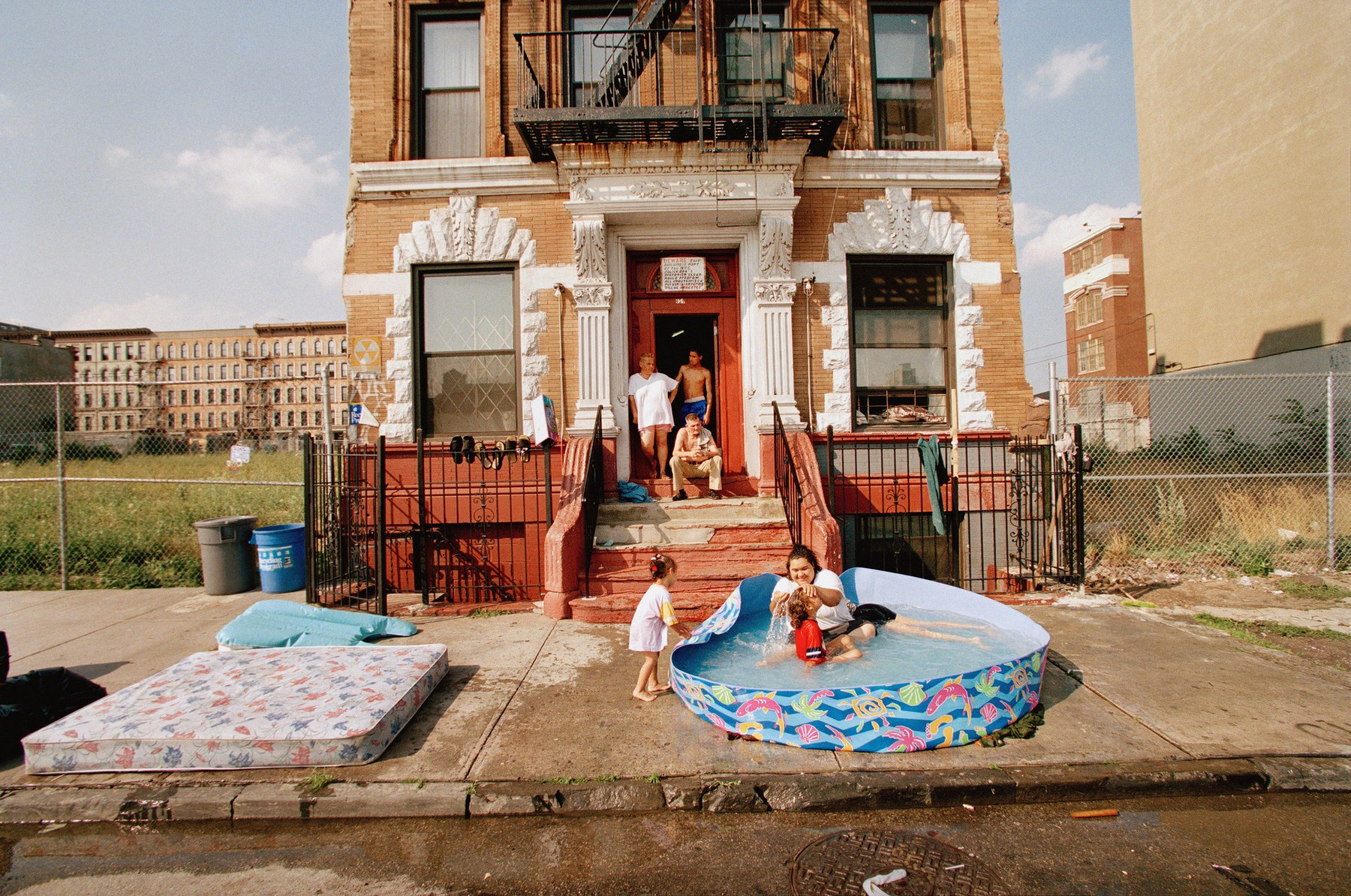 At 134th street in the South Bronx, a wading pool was a source of relief for bathers of all ages. July 1999. Credit James Estrin/The New York Times