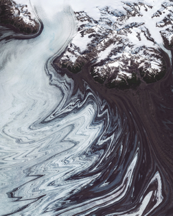 """""""Glacial ice and debris form incredible patterns around the edges of the Malaspina Glacier in southeastern Alaska. Located at the head of the Alaska Panhandle, the glacier is roughly 40 miles (65 km) wide and 28 miles (40 km) long, covering an area of about 1,500 square miles (3,900 square km). Decades of aerial photographs and radar data have shown that the Malaspina Glacier lost about 66 feet (20 m) of thickness between 1980 and 2000 — enough shrinkage to contribute 0.5% of the rise in global sea level."""""""
