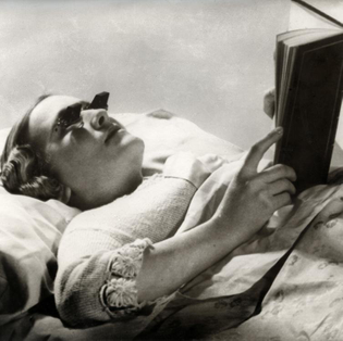 Reading in bed while lying flat on your back.