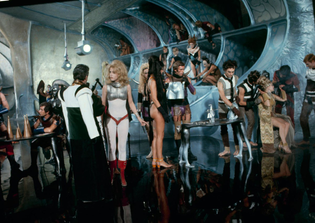 08-Jane-Fonda-in-white-and-other-cast-members-on-the-set-of-Barbarella-1968.jpg