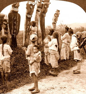 Worshipping the Sindo gods in front of wooden statues by a roadside in Seoul, about 1900