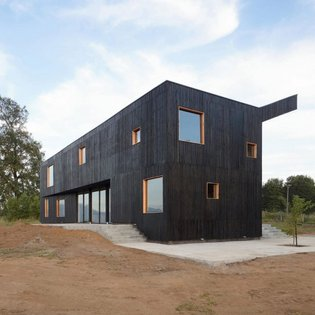 architecture firm Ampuero Yutronic has designed a double story stained-black wooden home: 'Casa Hualle'