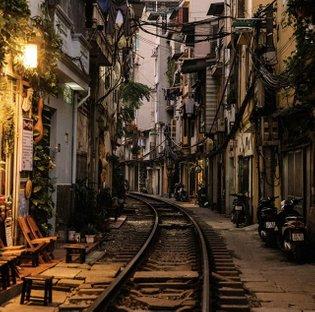 Photo by @hannahreyesmorales | In a bustling Hanoi neighborhood, trains run through a narrow street where residents nonchala...
