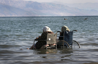 Elderly Palestinian women sit in wheelchairs as they enjoy the waters of the northern part of the Dead Sea, in the West Bank, on October 2, 2008.