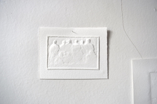 A blind-embossed piece of paper shows a silhouette of a group family photo.