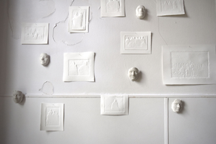 On a cracked white wall are plaster casts of tiny faces and embossed paper pieces.