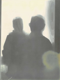 A lumen print of silhouetted figures. It is my grandmother holding me as a baby. The image is soft.