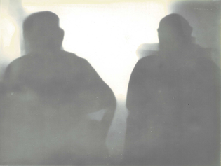 A lumen print of two seated figures.