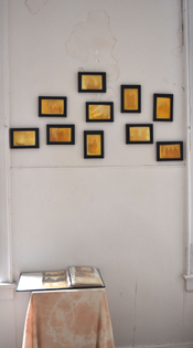 Several black framed turmeric prints hang on a cracked white wall. The turmeric prints are bright and deep yellow.