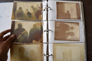 A hand opens an family album filled with lumen prints of silhouetted figures