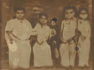 A sepia-toned lumen print of a machine generated image of what appears to be a family sitting together. The image is distorted.