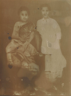 A sepia-toned lumen print of a machine generated image of what appears to be a couple. The image is distorted.