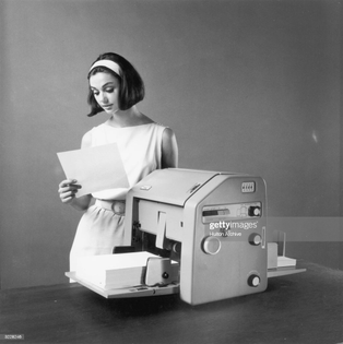 circa-1960-studio-image-of-a-woman-standing-behind-a-mimeograph-at-picture-id3228246