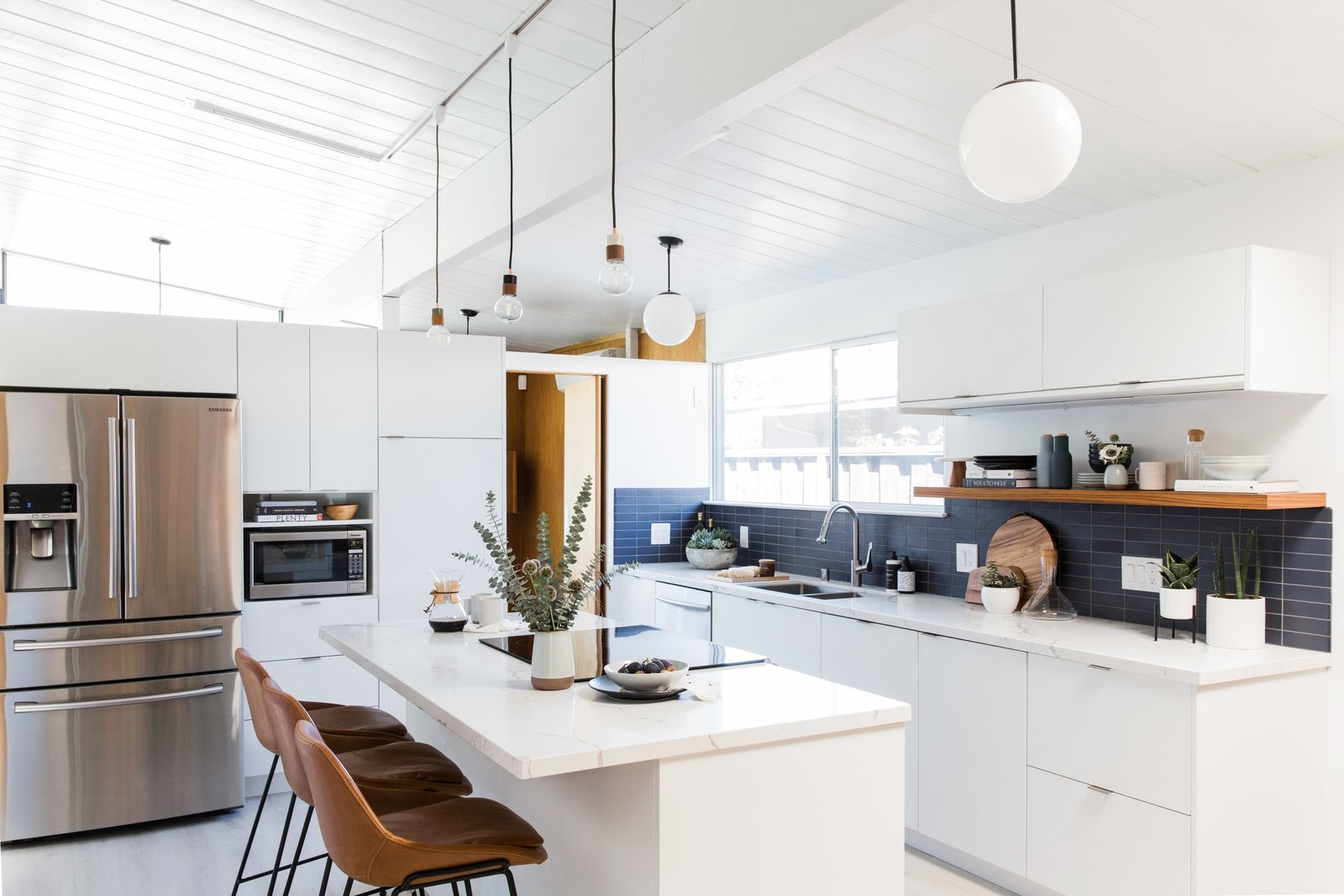 the-once-dim-cramped-kitchen-in-this-1963-eichler-in-san-jose-california-now-features-luxe-vinyl-tiling-white-slab-fronts-fr...