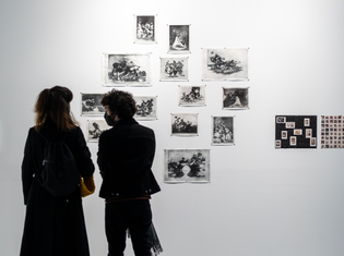 A gallery view of the installation. Several intaglio prints are pinned to a white wall and two people are chatting in front of it.
