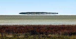 fata-morgana-mirage-looks-like-ufo-above-desert-flying-saucer-etosha-pan-namibia-africa-invasion-aliens-87595030.jpg