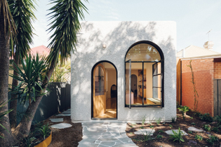 with-its-stucco-facade-and-steel-framed-arched-windows-plaster-fun-house-is-an-architectural-anomaly-amidst-the-cottages-and...
