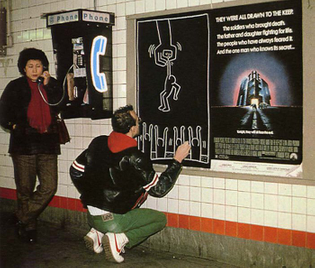 Keith Haring drawing in the subway next to a poster for The Keep, 1983