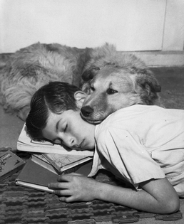 Boy and dog resting on doormat 1940