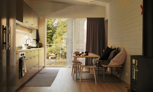 the-minimalist-eat-in-kitchen-features-gray-glulam-cabinetry-a-larger-dining-table-is-located-on-the-deck.jpg