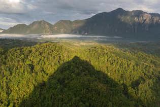 conical_shadow_of_mount_nam_xay_over_green_trees_at_golden_hour-_south-west_view_from_the_top-_vang_vieng-_laos_-cropped-.jpg