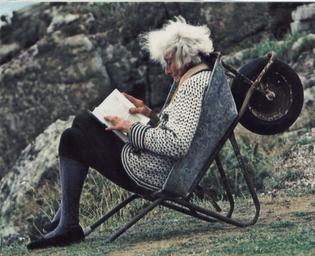 Rowena Cade reading in a wheelbarrow, 1977