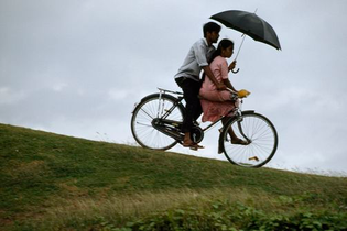 A couple riding a bike while holding an umbrella, Sri Lanka, James L. Stainfield.