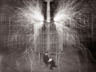Nikola Tesla is captured in a multiple-exposure photo in 1899, while a Tesla coil discharges millions of volts.