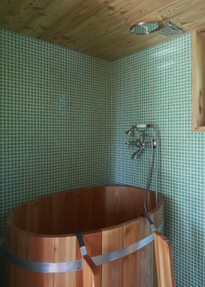 brilliant-green-mosaic-tile-covers-the-walls-and-the-floor-of-the-bathroom-where-the-architects-arranged-a-varnished-wood-so...