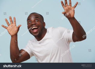 stock-photo-handsome-bold-black-man-in-white-t-shirt-is-smiling-against-pale-blue-background-razy-eyes-1289863630.jpg