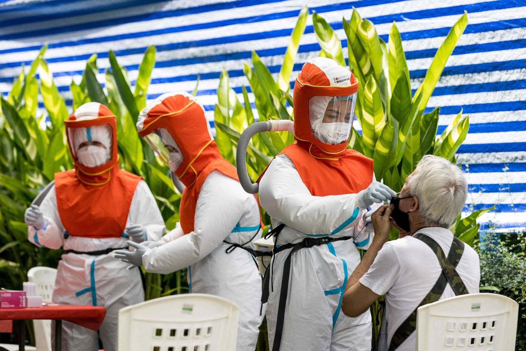 Bangkok health workers adminster nasal swabs