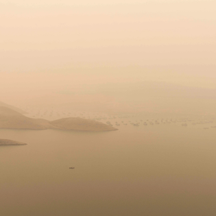 A shroud of smoke from the Dixie Fire over Lake Oroville in Northern California on the same day water levels fell so low that the dam's electricity-generating turbines shut down (Kevin Cooley / Redux)