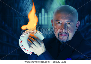 stock-photo-magician-man-posing-with-deck-of-cards-spread-out-in-his-hand-with-fire-and-gothic-background-288204326.jpg