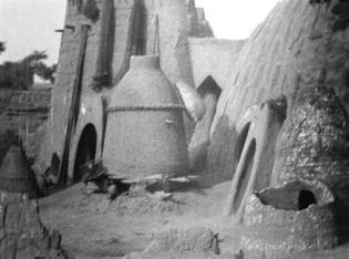 Cases en pisé en forme d'obus, appelées tolek et d'un silo à grain