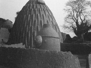 cases en pisé en forme d'obus, appelées tolek et d'un silo à grains