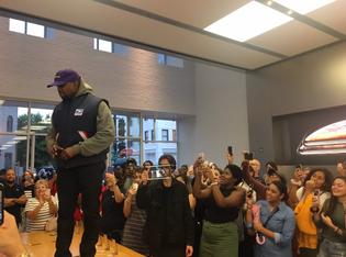 Kanye standing on a table at the Apple store