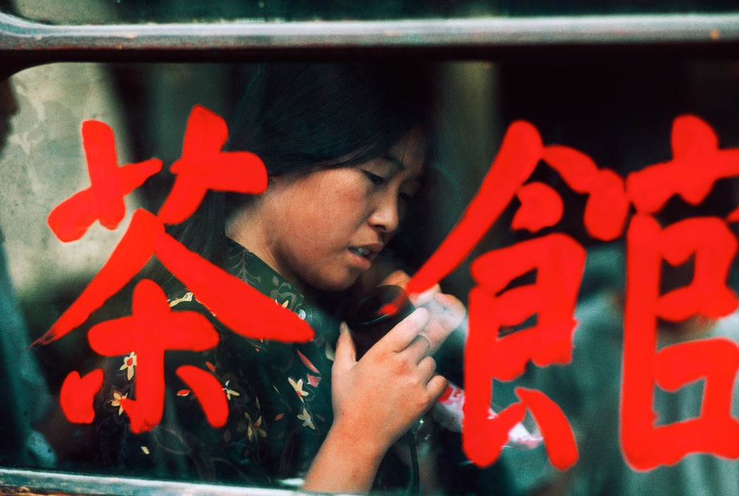 Girl in telephone booth in old town, Beijing, China (1984)