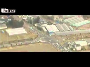 Aerial view of tsunami striking Sendai Japan