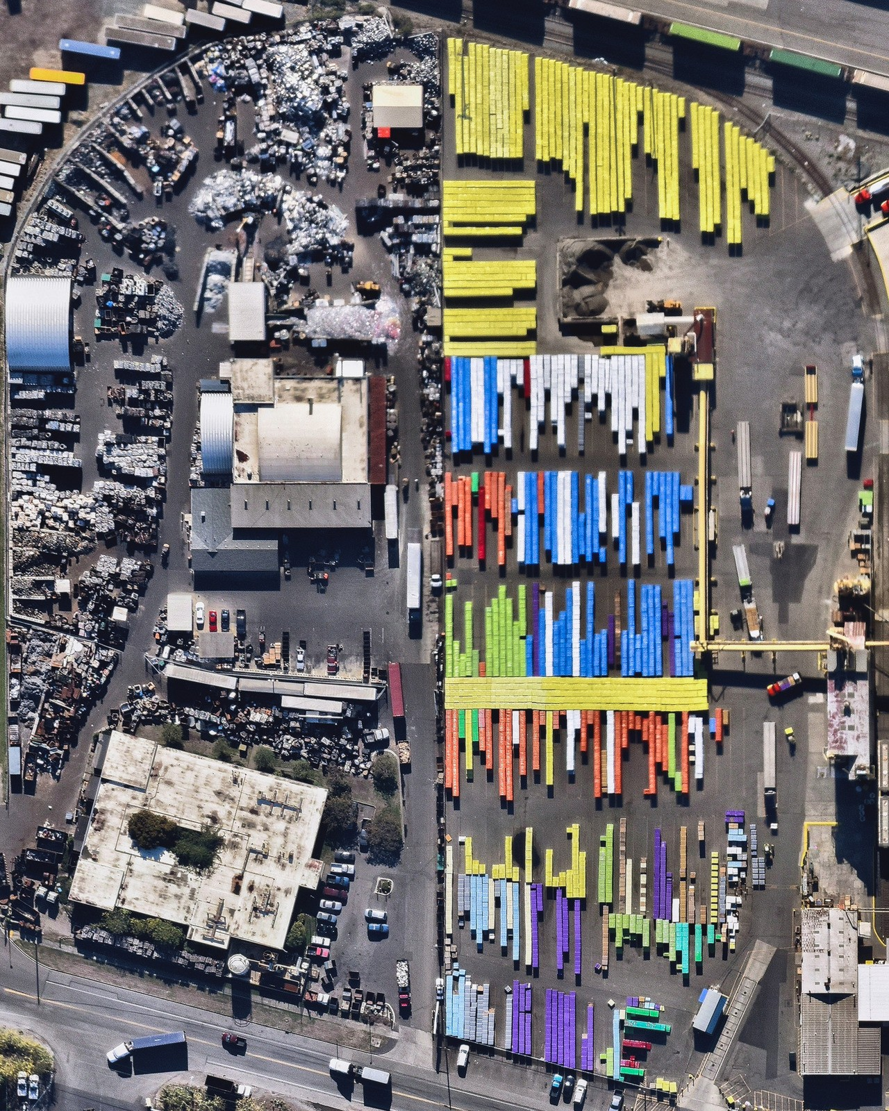 """""""Brightly colored shipping containers are stacked next to a scrap metal storage yard at the Port of Tacoma, Washington."""""""