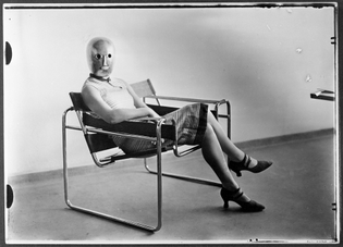 Woman wearing a theatrical mask by Oskar Schlemmer and seated on Marcel Breuer's B3 chair, c.1926